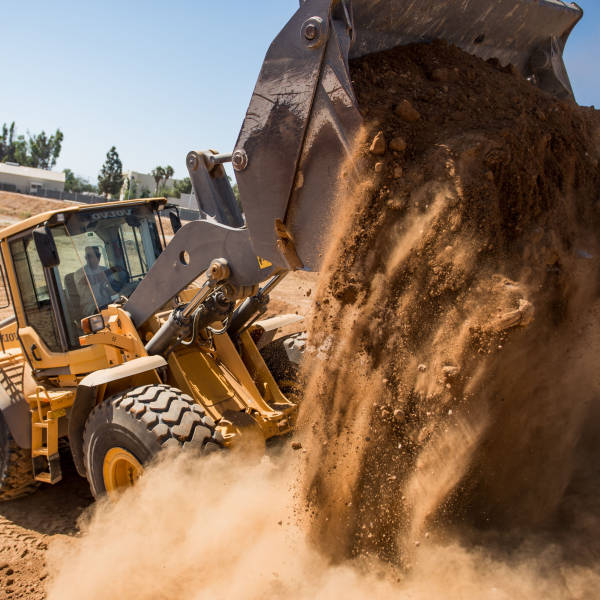 Managed IT Services for Civil Construction. A bulldozer tips a pile of dirt