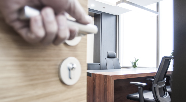 Return to Office. A hand opens an office door as the occupant returns to work